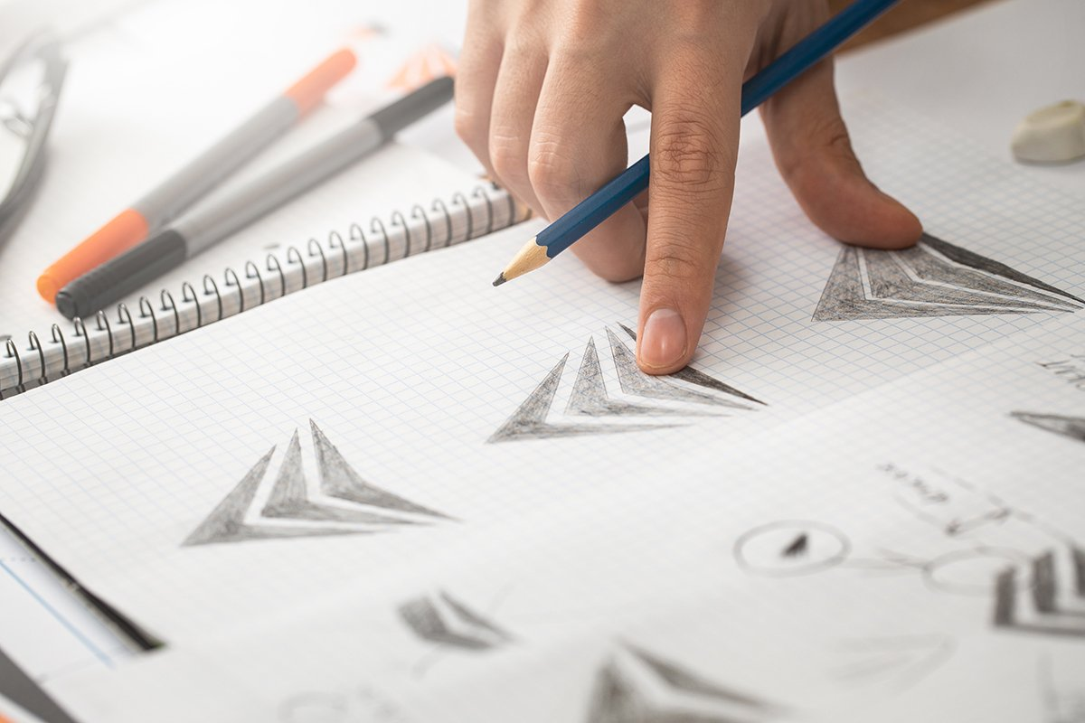 pointing at sketch of hand drown logo visually expressing your why