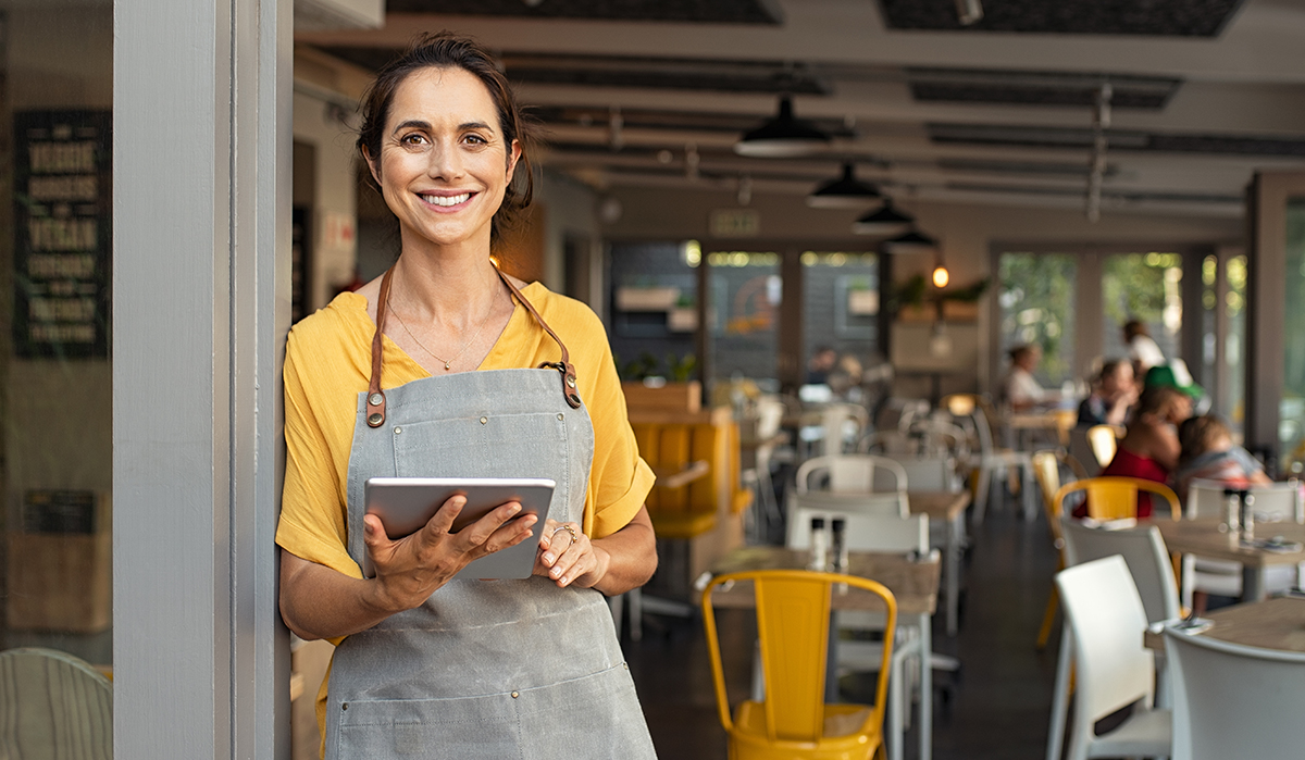 restaurant owner at entrance with pos tablet experience